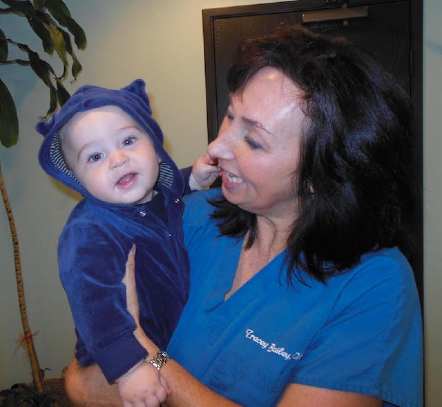 Dr. Tracey holding baby in blue